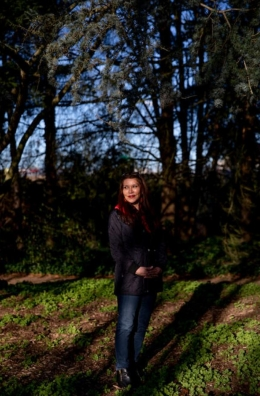 Professor Charlotte Cote standing in a wooded area