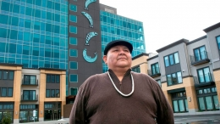 artist Joe Seymour in front of his installed salmon artwork